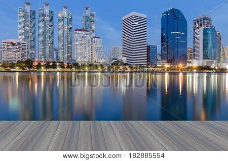 Opening wooden floor Office building with water refleciton with blue twilight sky background