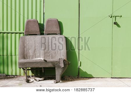 Discarded Car Seats In Front Of A Green Garage Door