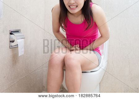 woman feel pain with constipation in the bathroom