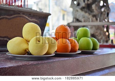 Yellow pears, oranges and green apples fruit offerings as a sacrifice at Chinese temple.