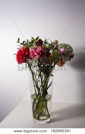 Slightly Wilted Flowers In A Transparent Vase