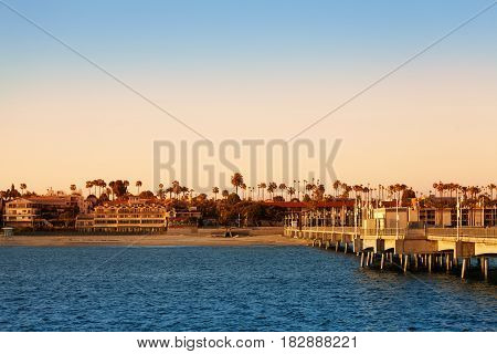 Beautiful evening scenery of Long Beach coastline with hotels, palm trees and pier on poles