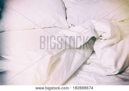 White bedding background. Crumpled bedclothes vintage film lighting effect. Morning glow.