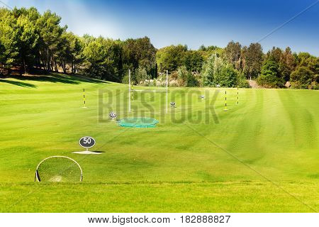 Flagsticks, markers and bunkers at the golf course in the midst of beautiful green wood