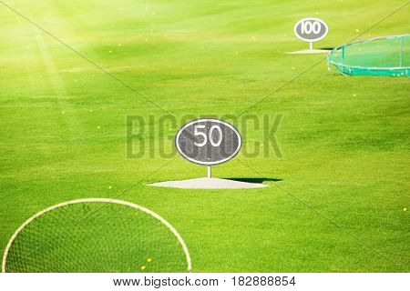 Driving range at golf course with yard signs and a lot of yellow balls on the grass