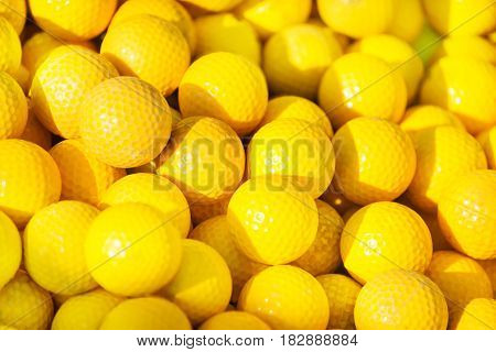 Pile of yellow golf balls with patches of sunlight, close-up
