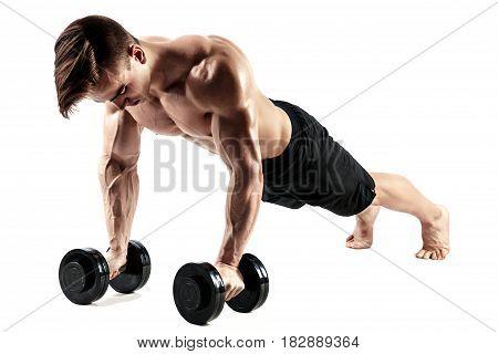 Muscular bodybuilder guy doing Push-ups on dumbbells from the floor over white background