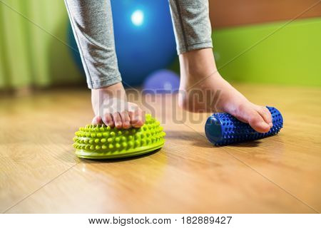 Flat feet correction exercise. Girl stepping in to spiked rubber roller