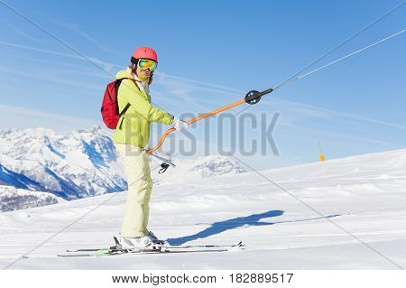 Portrait of female skier lifting on button lift at sunny snowy day