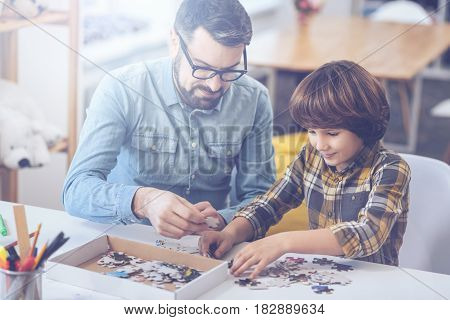 All-in-the-family time. Young father holding a puzzle piece in his hand while spending free time with his little son