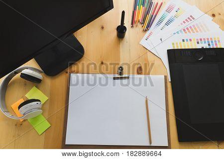 Desk Of Graphic Designer At Work - Digital Tablet, Computer Screen, Color Swatch Catalog Samples For