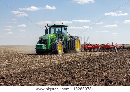 Kharkiv Ukraine - April 13 2017: Tractor with trailed planter working in field in a sunny spring day in Kharkiv Oblast Ukraine on April 13 2017