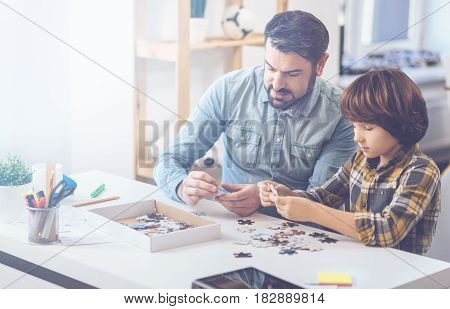 Brain-taxing work. Handsome father and concentrated son looking at puzzle pieces while having fun on weekends