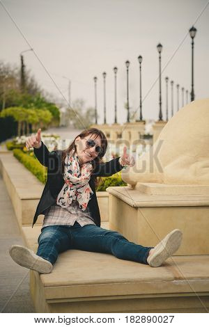 Young Smiling Happy Girl In Sunglasses, Black Jacket And Anchors Scarf Sitting Outdoors Showing Thum