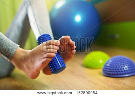 Flat feet correction exercise. Girl using spiked rubber roller