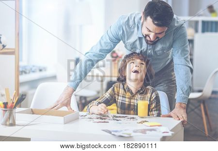Daddy, you are the best. Cuttest little boy laughing at a joke heartily and looking at his father while playing in family circle