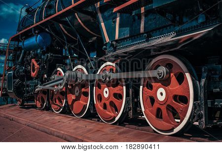 Vintage train close-up wheels view.  Dark blue and red color tinting.