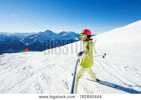 Happy female skier taking selfie photo using selfie-stick with beautiful mountains at the background
