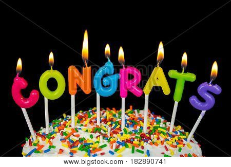 lit congrats candle on cake with candy sprinkles