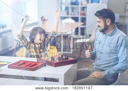 Checkmate. Riant cute boy showing vivid emotions and raising his arms in victory on the chess board