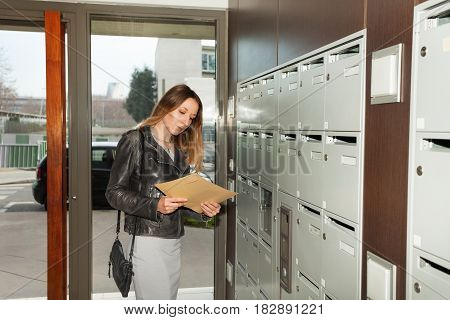 Portrait of pretty young woman taking envelope, standing next to the mailboxes at the porch