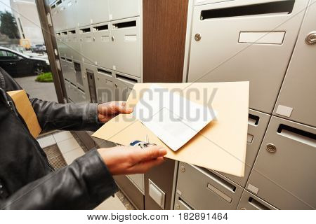 Picture of woman's hands holding envelopes next to the mailboxes at the doorstep