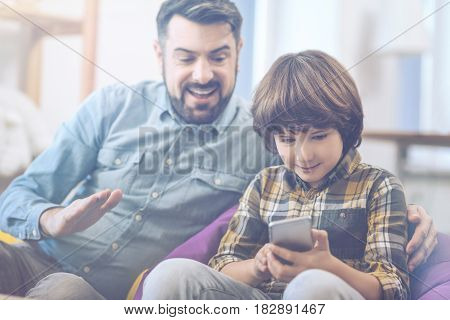 Yay, best score ever. Rident father watches his son playing with digital game on a cell phone while spending free time together