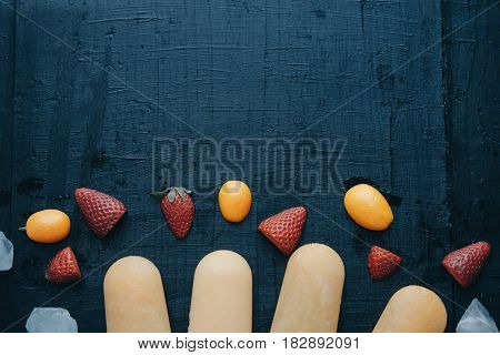 Top View Of Homemade Fruit Ice Cream With Strawberries And Kumquat On A Black Board.