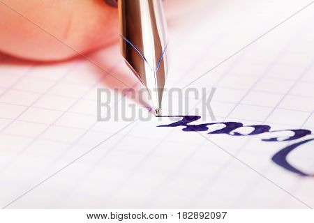 Close-up picture of fountain pen with blue ink writing on squared notebook
