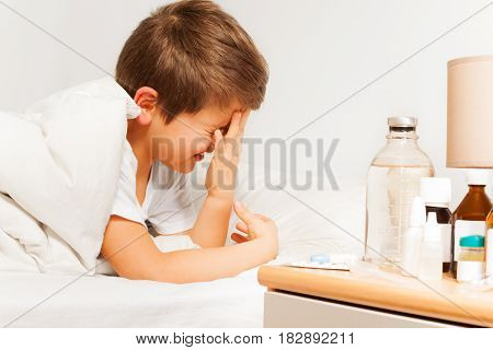 Crying kid boy laying in hospital ward or room bed with blanked medicaments bottles standing on the bedside chest