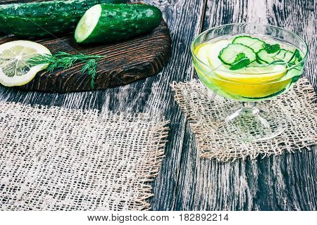 Detox water with lemon and cucumber. Drinking glass with slices of fresh fruit, dill and mint leaves and rosemary. Black and white wood background with burlap napkins. Selective focus