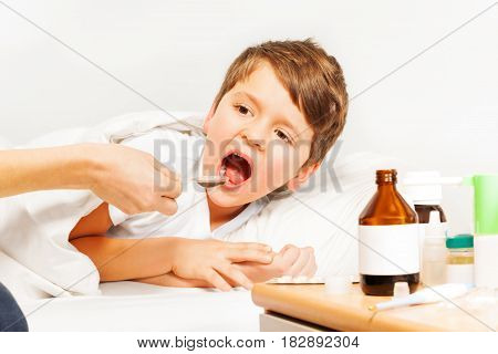 Sick Caucasian kid boy taking meds laying in  bed of hospital ward with blanked background