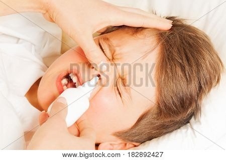 Close-up portrait of sick kid boy crying while mother spraying him nasal spray or drops in nose