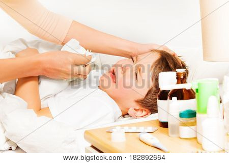 Little sick boy laying in bad and crying while mother helping to blow his nose with paper napkin