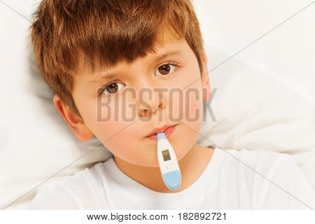 Close-up portrait of sick five years old boy taking temperature with electronic thermometer in bed