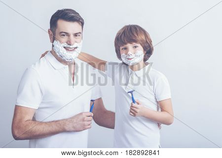 Like father, like son. Young father and his cute son posing with razors in their hands while having fun and shaving together