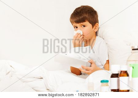 Five years old boy with bad cold sitting in bed and using paper napkins against white wall