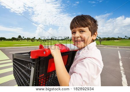 Close-up portrait of smiling five years old boy pushing the shopping cart at crosswalk of supermarket parking lot