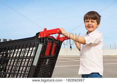 Side view portrait of smiling five years old boy pushing empty plastic shopping cart to the supermarket