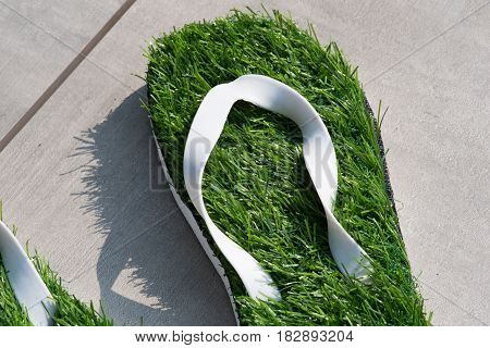Flip flops with green grass sole stand in the sun