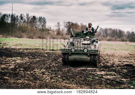 RIGA, LATVIA - APRIL 2017: Soldiers are driving on military caterpillar machine