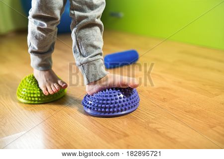 Flat feet correction exercise. Little boy walking over spiked half balance massage balls