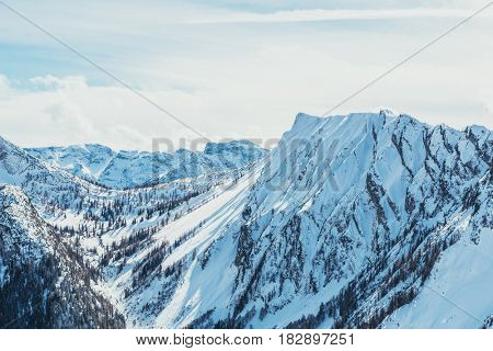 Snow covered mountainous landscape in winter with wooded slopes
