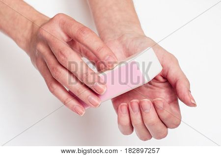 Close up woman's hands make filling nails on the light background