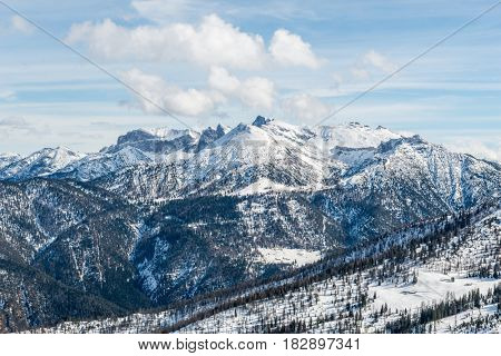 Wooded Alpine landscape with mountains in background, winter scene