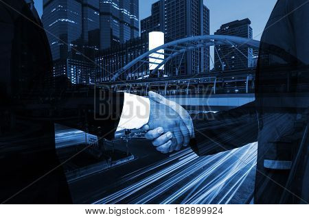 Double exposure of businessman handshake business concept successful business meeting on night city background color tone effect.