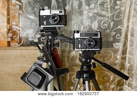 Two retro photo cameras on tripods front shot with focus in the foreground