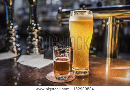 Light beer in a beer glass and dark beer in a small glass lighted with warm light on a wooden bar counter