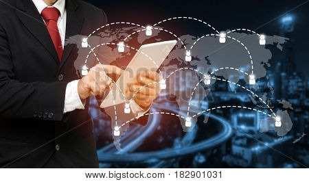 smart businessman in suit using his tablet business and technology concept with world map social media network connection on blurred night city background color tone effect wide screen.