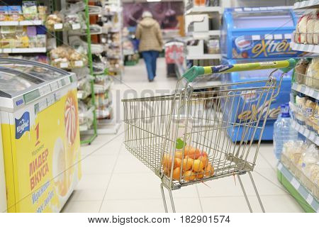 Kaluga, Russia - April, 21, 2017: Interior of a supermarket in Kaluga, Russia with shop trolley on a frontground